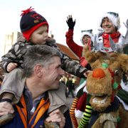 image of family enjoying entertainment in form of two elves on a reindeer at the Christmas Market