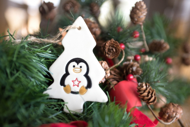 Christmas tree ornament in the shape of a tree with penguin on