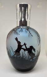 A handmade fragrance lamp with hares depecited on it
