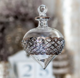 A handmade clear glass ornament with an engraved band of lattice work