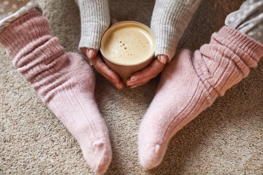 Socks being worn by a lady with hands around a hot drink in a mug
